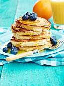 Pancake-Stapel mit Ahornsirup, Heidelbeeren und Orangensaft