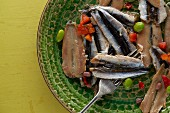 Cold smoked anchovy fillets with edamame and red pepper on rustic green textured plate on vintage yellow table