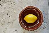 Lemon in vintage bowl on rustic marble table
