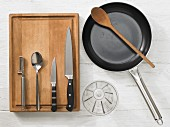 Various kitchen utensils: pan, spoon, measuring cup, peeler, knives