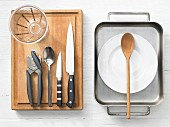 Various kitchen utensils: oven tray, measuring cup, can opener, knives