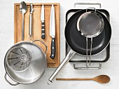 Various kitchen utensils: baking dish, pan, sieve, pot, measuring cup, knives