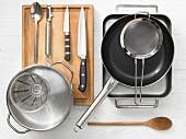 Verschiedene Küchenutensilien: Reine, Pfanne, Sieb, Topf, Messbecher, Messer