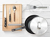 Various kitchen utensils: pans, spatula, knives, spoons