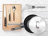Verschiedene Küchenutensilien: Pfannen, Pfannenwender, Messer, Löffel