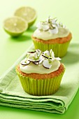 Fresh coconut and lime iced cupcakes on a green napkin and green background with 2 half limes