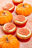Several Pumpkin pie cupcakes shown with real pumpkins on a light orange background