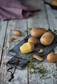 Potatoes, partly peeled, on a chopping board