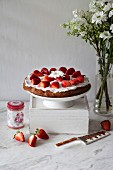 Strawberry cake with whipped coconut cream and topped with fresh strawberries on a white cake stand