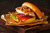 Burger with chicken breast and fried onions on dark background