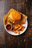 Burger with chicken breast and fried onions with potato wedges on plate on dark wooden background