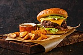 Pastrami Burger with sliced Roast beef and potato wedges on dark background
