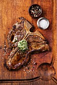 Grilled T-Bone Steak and herb butter on wooden cutting board