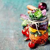 Frische Zutaten für Gemüsesalat in Einmachglas geschichtet
