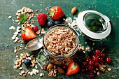 Healthy breakfast of muesli, berries with yogurt and seeds on dark background