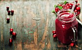 Cranberry smoothie on rustic wooden background