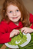 Child shelling peas on a kitchen table