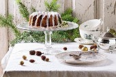 Christmas homemade cake with frosting served with christmas tree branches, vintage tableware and decor