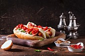 Homemade hot dogs on wooden plate with ingredients mustard, tomato sauce, onion, pepper, rosemary