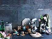 Küchenutensilien, -geräte und Kleingebäck auf schwarzer Tischplatte