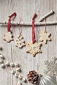 Aufgehängte Weihnachtsplätzchen in Form von Bäumen und Schneeflocken mit Zuckerglasur