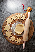 Cookie dough on a floured wooden chopping board surrounded with cutter out snowflake shapped biscuits next to a rolling pin on a grey slate background