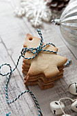 Stack of Christmas tree shaped biscuits tied with blue and white baker twine on a rustic white wood suface and surrounded with Christmas baubles and bells