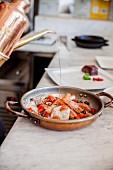 Garnelen, Tintenfisch und Kirschtomaten in Kupferpfanne mit Öl begiessen
