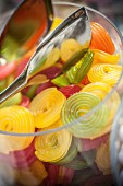 Fruit gummy wheels in a glass jar with tongs