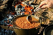 The hand of man stirring beans with a ladle over a campfire