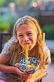 Noodles hanging from the mouth of a young girl holding a bowl