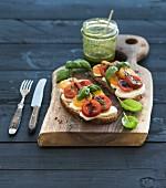 Tomato, mozzarella and basil sandwiches on dark wooden chopping board, pesto jar over black background