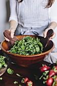 Frau bereiitet Spinat-Rucolasalat mit Erdbeeren in Holzschale zu
