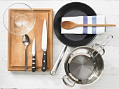 Various kitchen utensils: pan, pot, strainer, glass bowl, knives, spoon