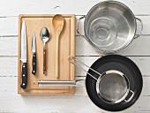 Verschiedene Küchenutensilien: Topf, Pfanne, Sieb, Messer, Löffel