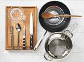 Various kitchen utensils: pot, strainer, pan, measuring cup, citrus press
