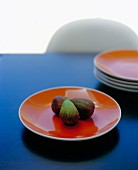 Fresh figs on an orange plate on a blue table