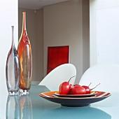 Obstschale mit Tamarillos und zwei Glasvasen auf Glastisch
