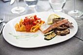 Tagliatelle with tomatoes and a salmon fillet with grilled vegetables