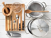 Various kitchen utensils: Pots, strainer, mortar, can opener