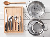 Various kitchen utensils: pots, strainer, measuring cup, can opener, knives, spoon