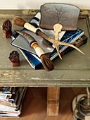 Pinsel mit Horngriffen und ein Stapel Bücher auf einem Tisch