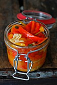 Italian Pickled Peppers in a Jar on a rustic wood background