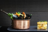 A copper saucepan of mussels with prawns, corn and vegetables served with a stack of chunky chips