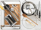 Various kitchen utensils: pasta machine, potato press, pastry wheel, pot, pan