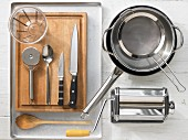 Various kitchen utensils: pasta machine, pot, pan, sieve, measuring cup