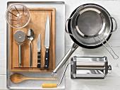 Verschiedene Küchenutensilien: Nudelmaschine, Topf, Pfanne, Sieb, Messbecher