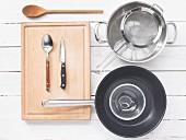 Verschiedene Küchenutensilien: Topf, Sieb, Pfanne, Löffel, Messer