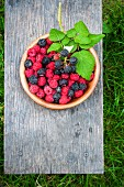 Fresh raspberries and blackberries in a bowl on a wooden board