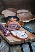 Homemade hard cured sausage and ham on a chopping board